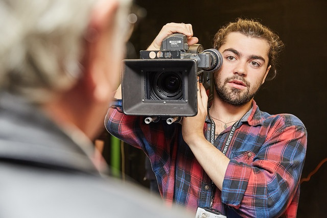 male film study student holding camera