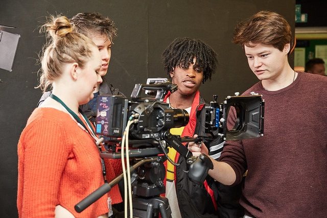 four film studies students around a camera