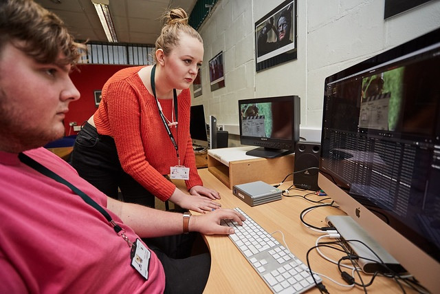 two film studies student behind a desk editing