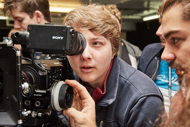 male film student looking down the camera lense