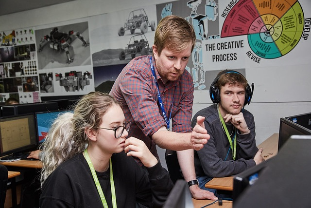 lecturer showing talking to his games development students