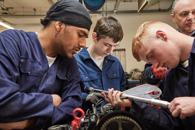three automotive maintenance students working on equipment