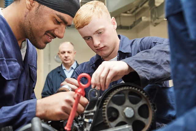 two automotive maintenance students working on equipment whilst lecturer supervises