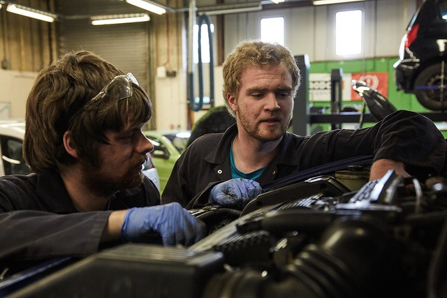two male automotive maintenance students looking inside car bonnet