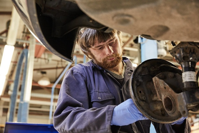 male automotive maintenance student working on a wheel