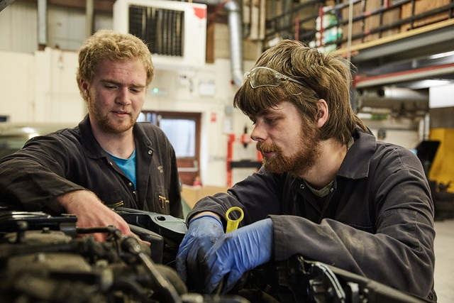 two male automotive students looking inside car bonnet
