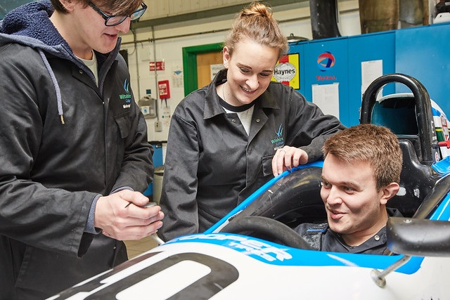 motorsport engineering students together, one sat in a race car