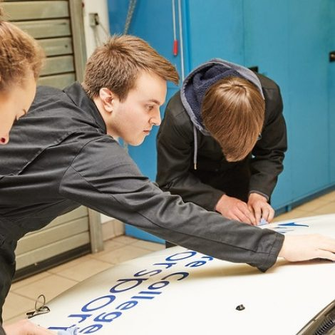 four motorsport engineering students working on a car
