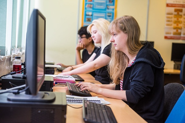 several students sat behind the desk