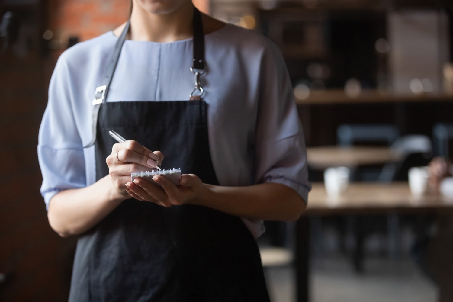 waitress wearing black apron standing with notepad in hand