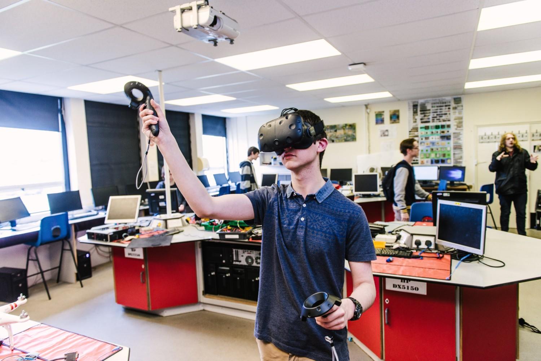 student stood up playing on virtual reality headset