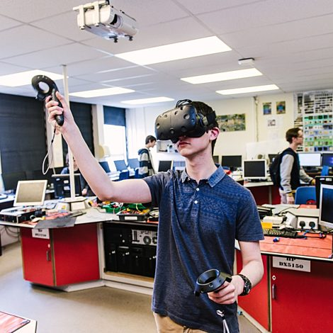 student stood up playing on virtual reality headset