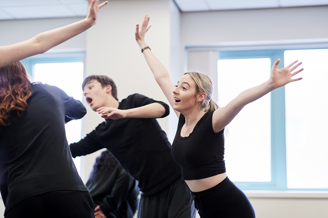 Three students in black are acting, their arms raised in the air.