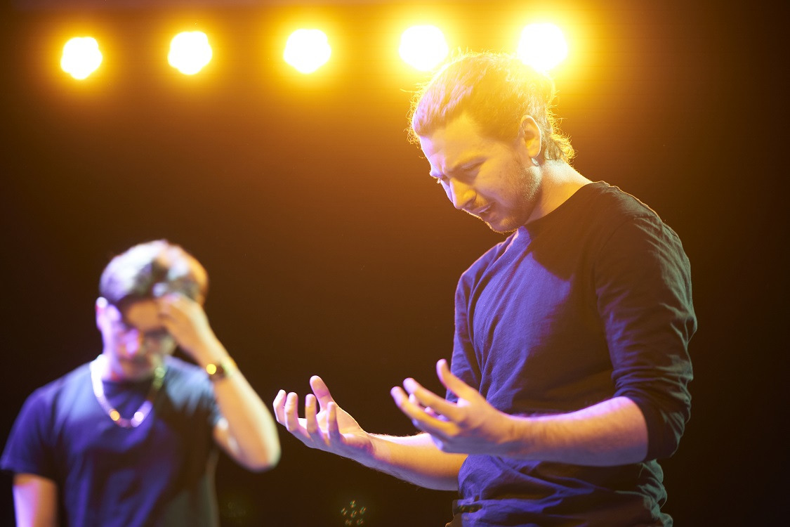 A student is acting beneath stage lights, holding his hands in front of him. Another student stands in the background.