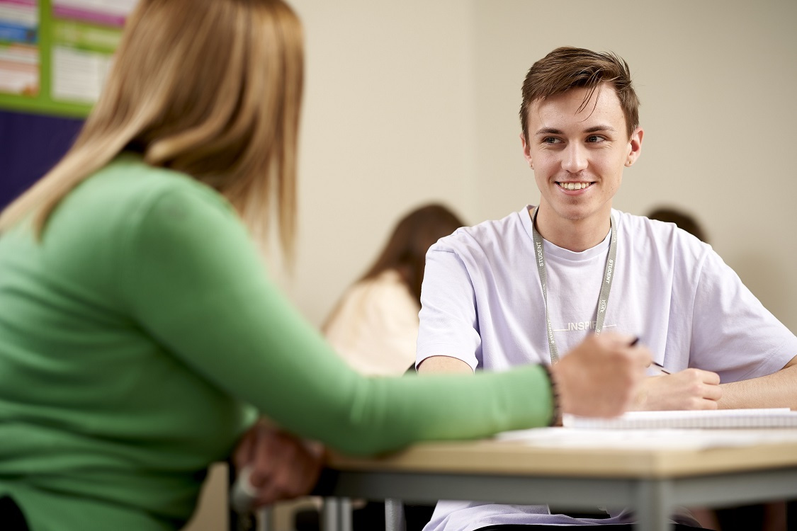 A student smiles and chats with a tutor