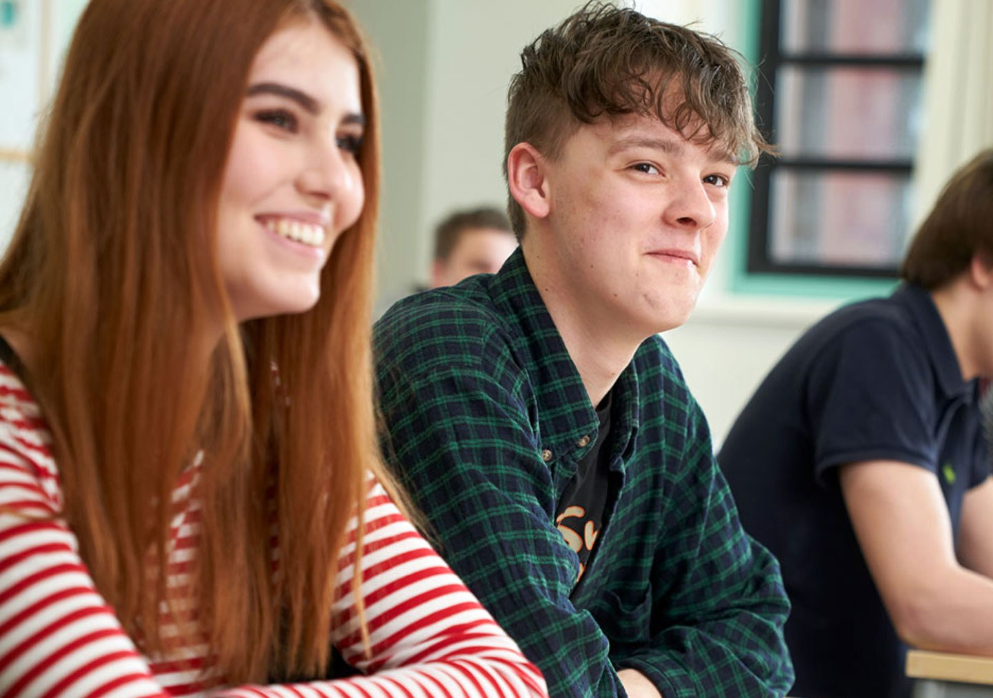 Two students smiling as they listen in the A Level Business class