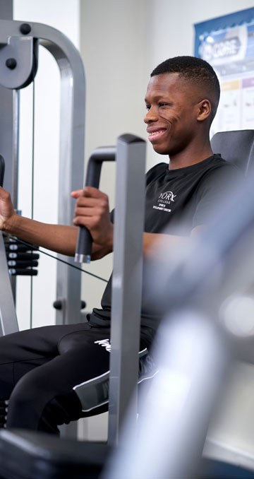 A student exercises on a machine in the gym