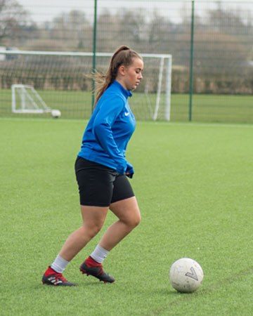 A student is on the football pitch dribbling a football