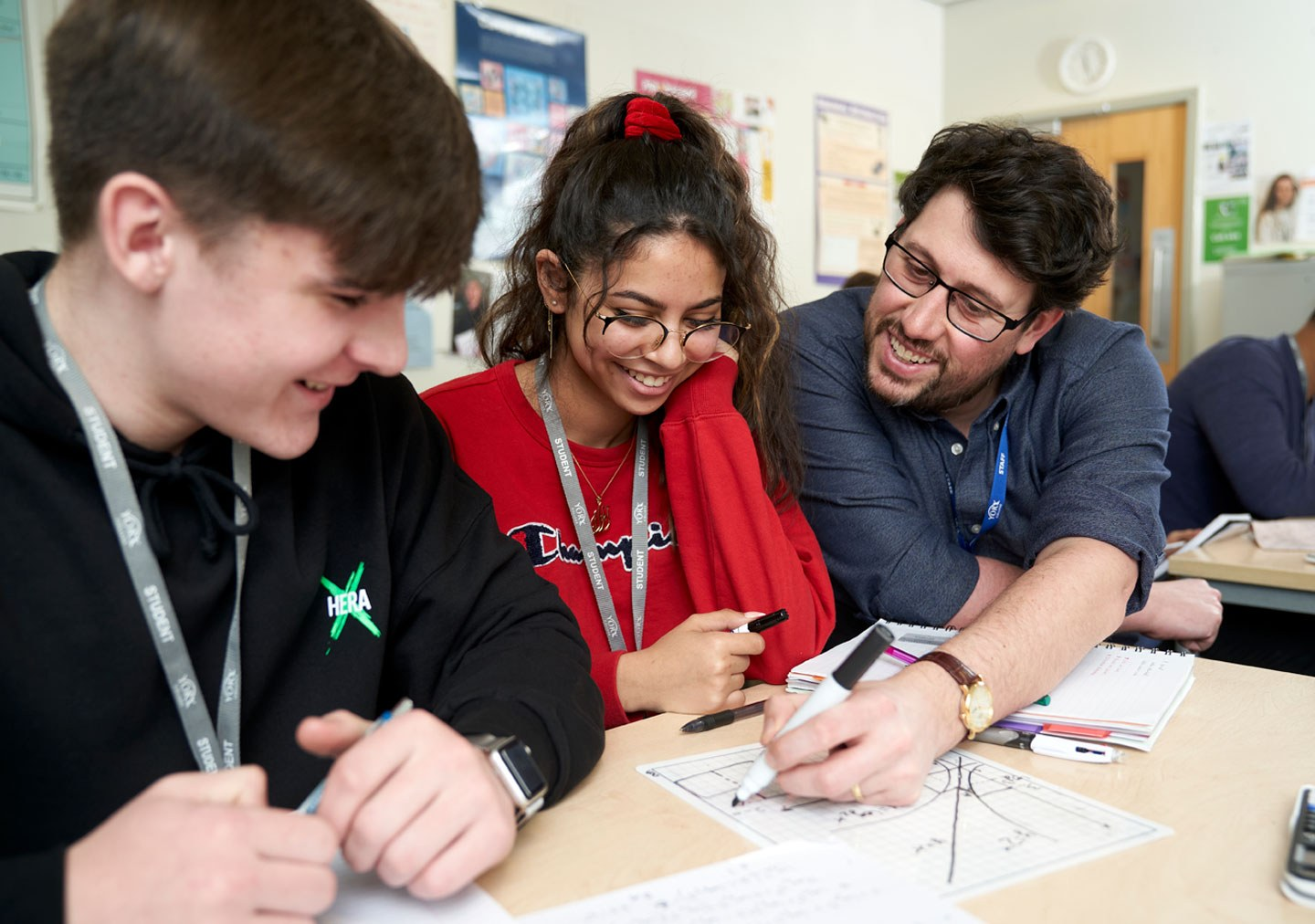 A tutor is helping two students with their work and is drawing a graph they are all smiling