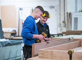 Apprenticeship bench joinery student in workshop attaching hinges to a door