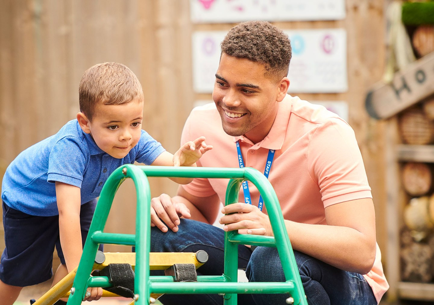 Childcare student in chilcare setting helping a child on some outside play equipment