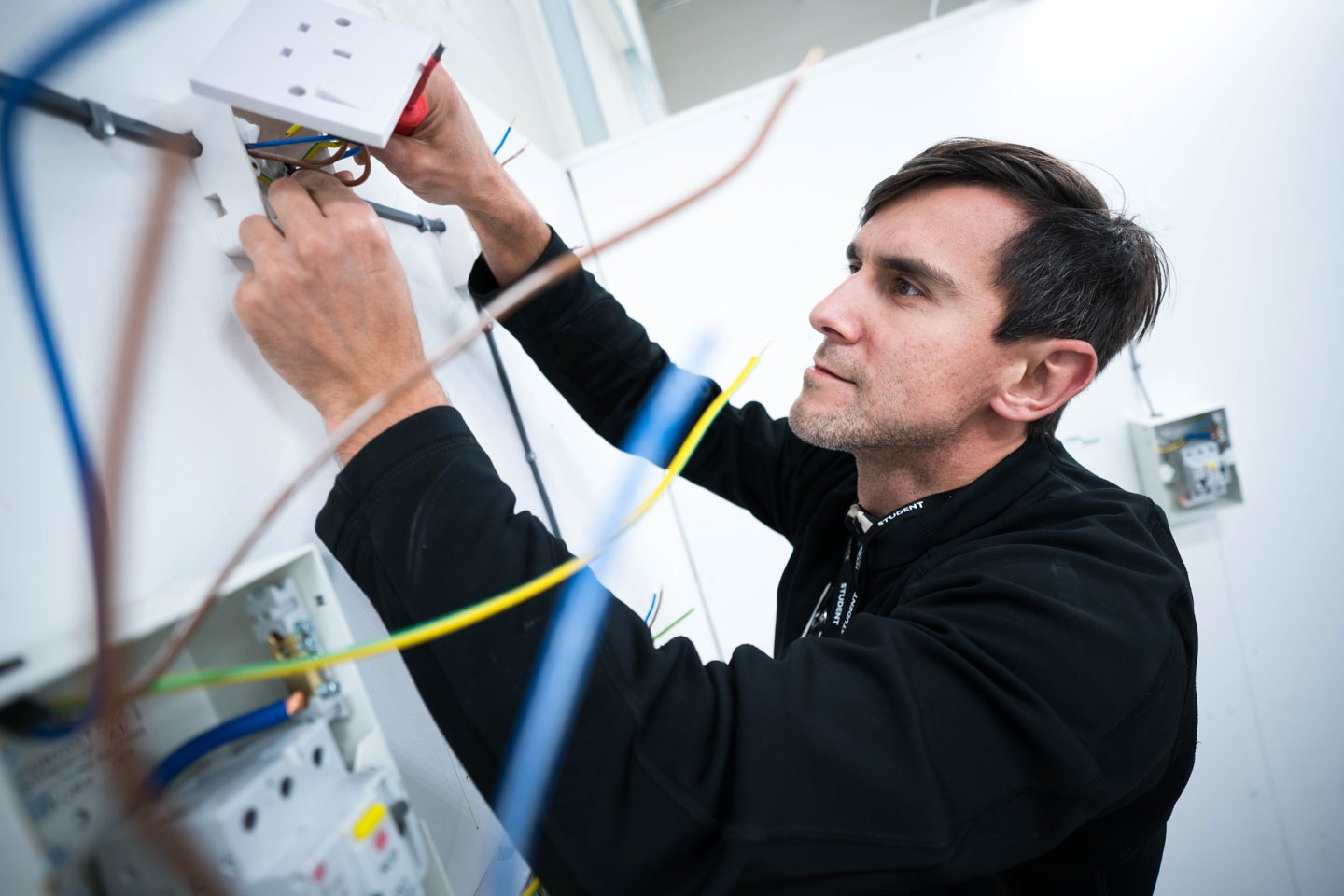 Electrician adult student working on a plug