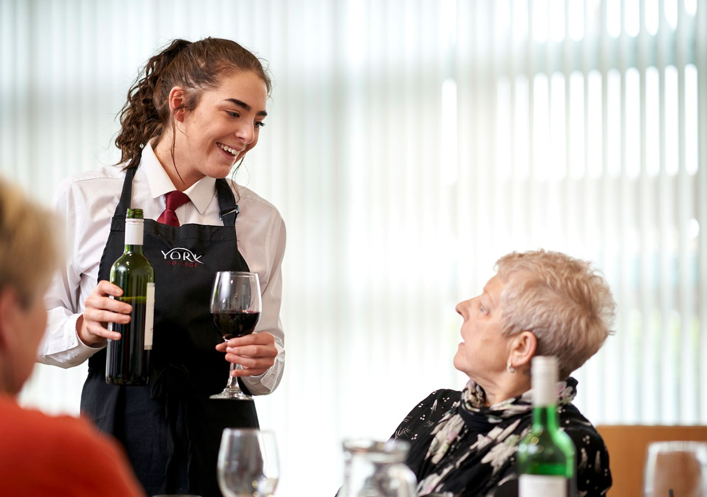 Hospitality student serving wine to a customer in Ashfields Restaurant