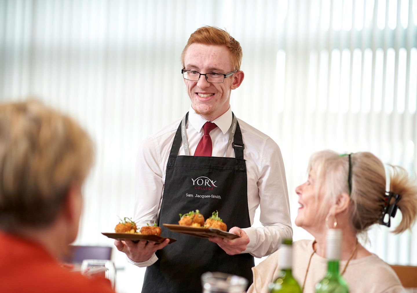 Hospitality student serving customers in Ashfields Restaurant