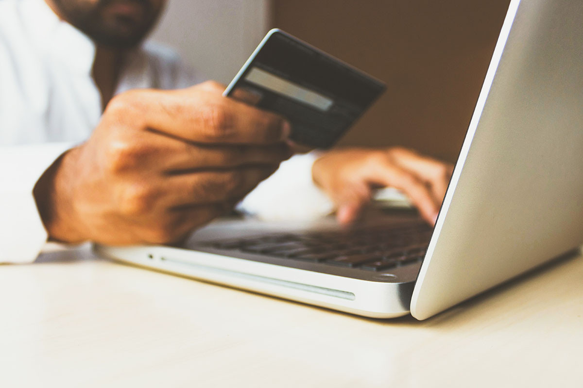 Image of person at laptop with credit card in hand
