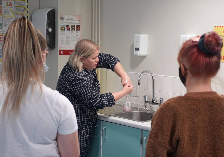 A tutor demonstrating correct handwashing procedures to students