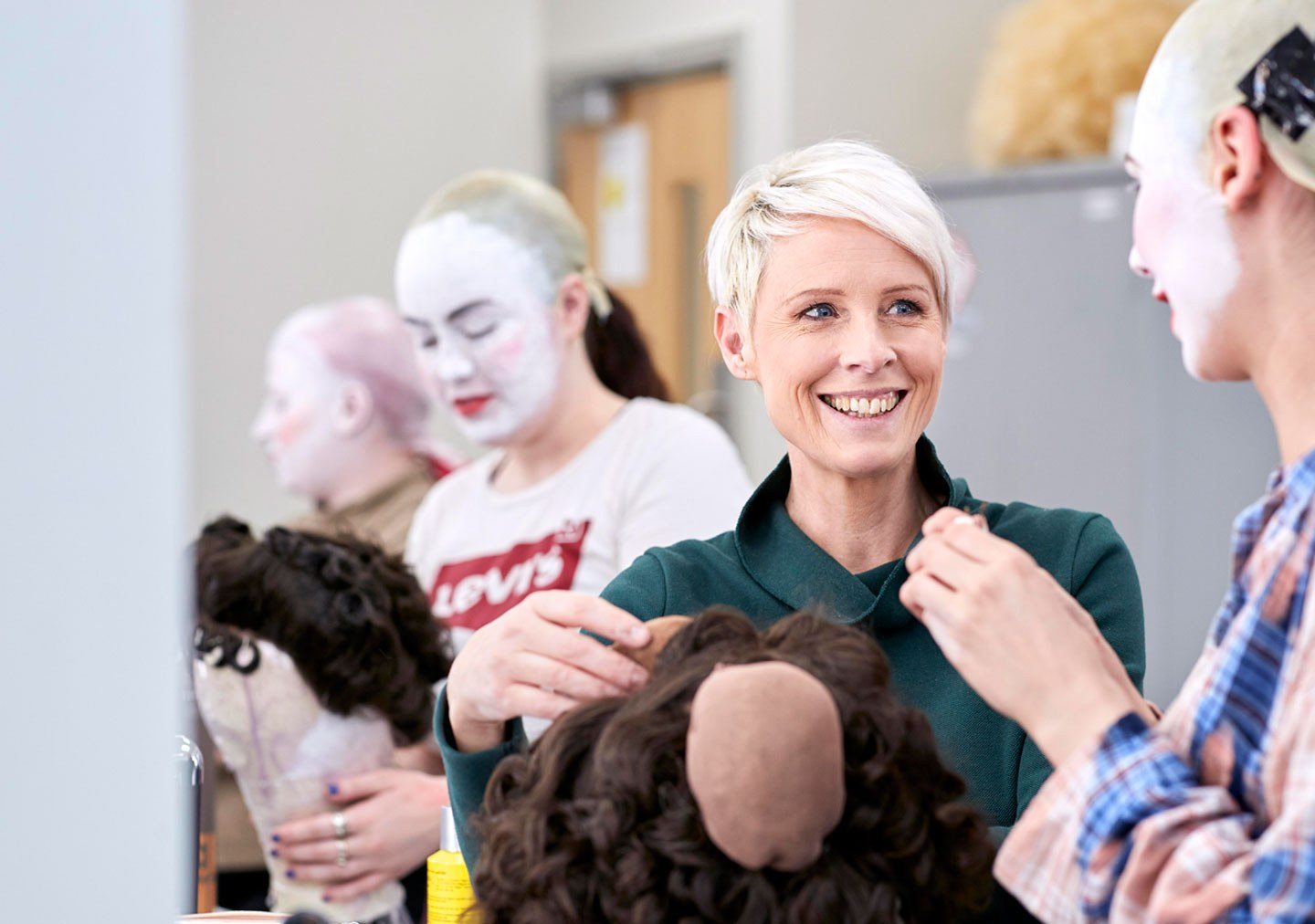 Media make up tutor talking to student during a final project working on a wig