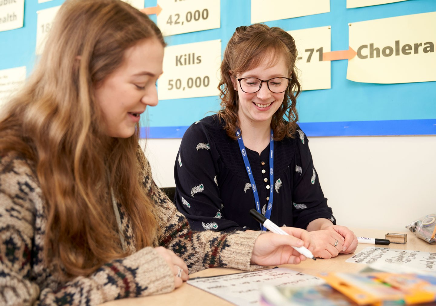 A tutor works with a student in Modern History
