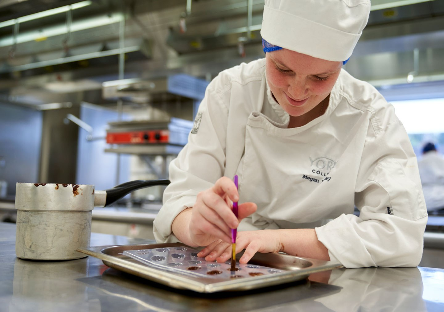 Patisserie and Confectionery student putting chocolate in to moulds