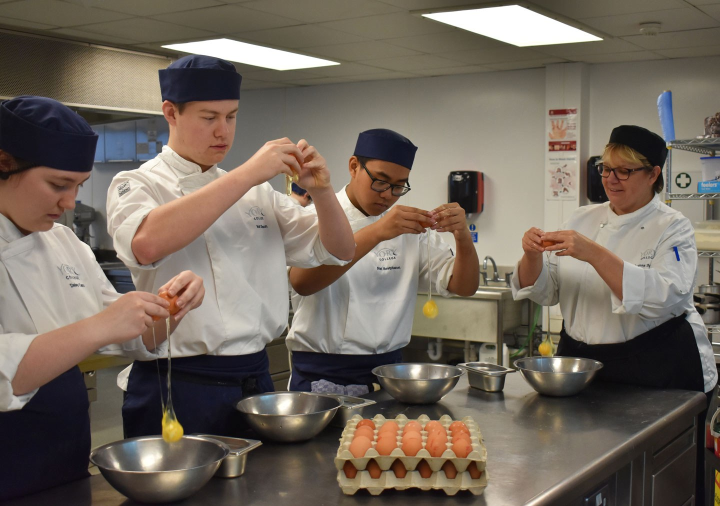 Three students and a tutor cracking eggs in to bowls