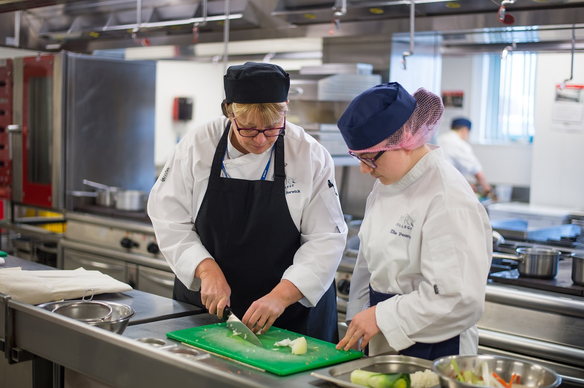 Professional Cookery tutor showing a student how to chop vegetables
