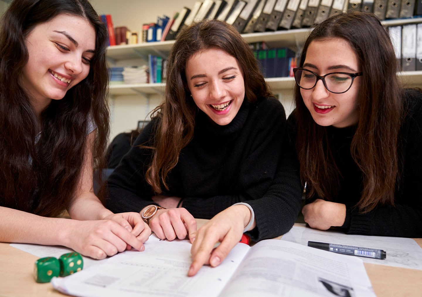 Three students are smiling and looking at a Spanish textbook
