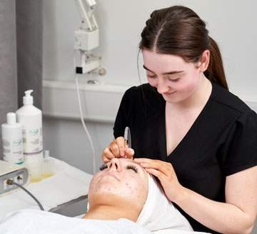 Student giving facial treatment