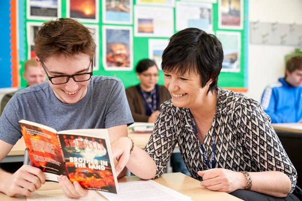 Student reading and being supported by a tutor