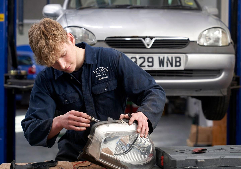 Student repairing a car headlight on the Light Vehicle Maintenance Level 1