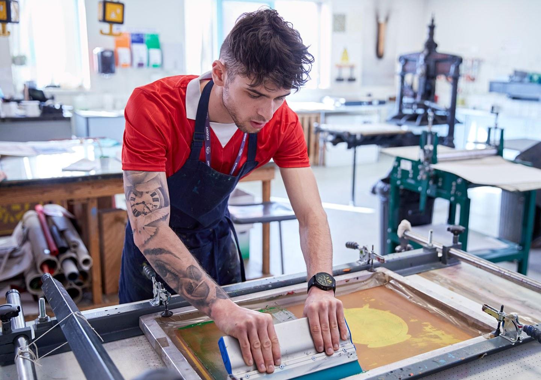 Student screen printing in print room