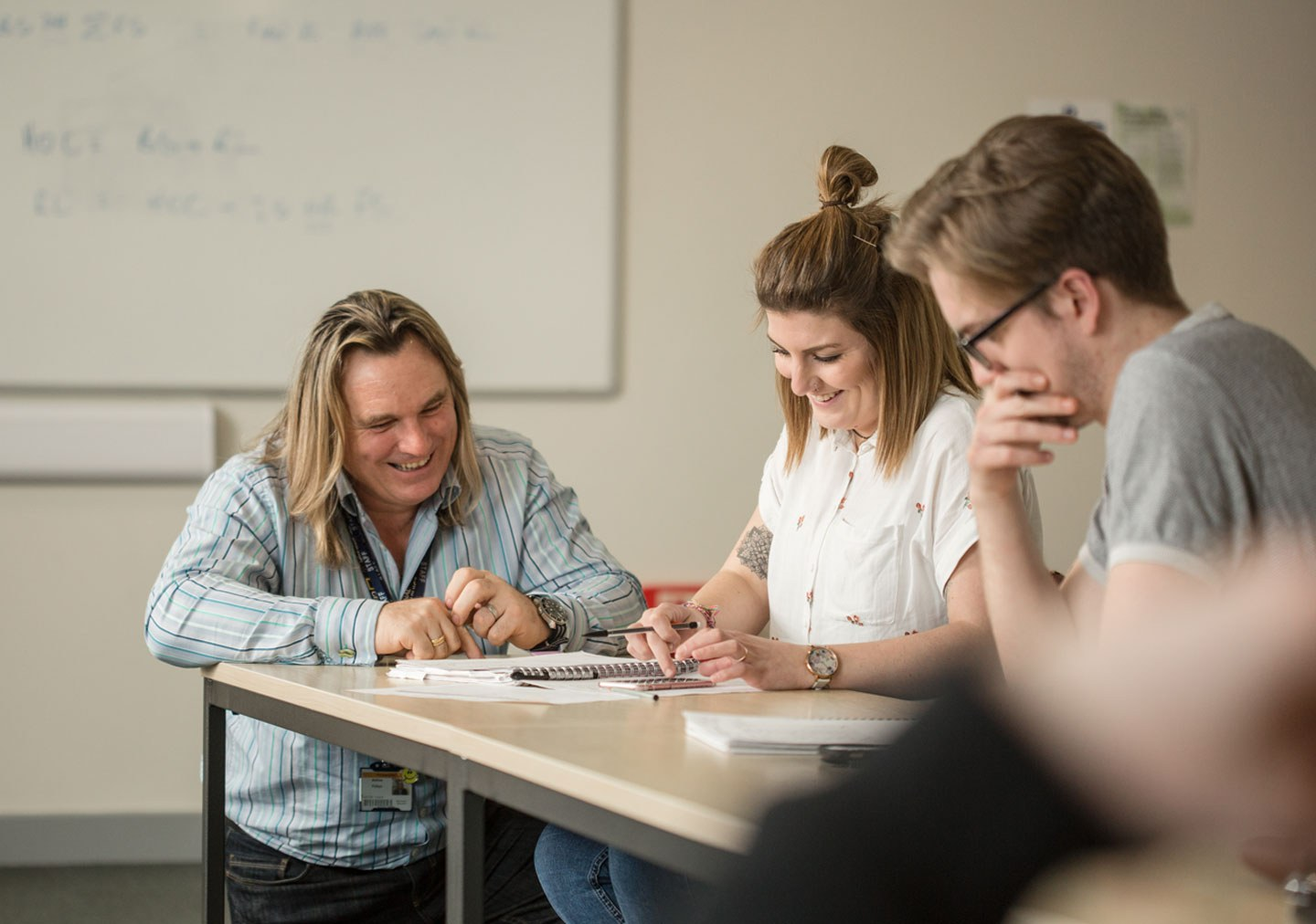 Tutor assisting construction student in classroom