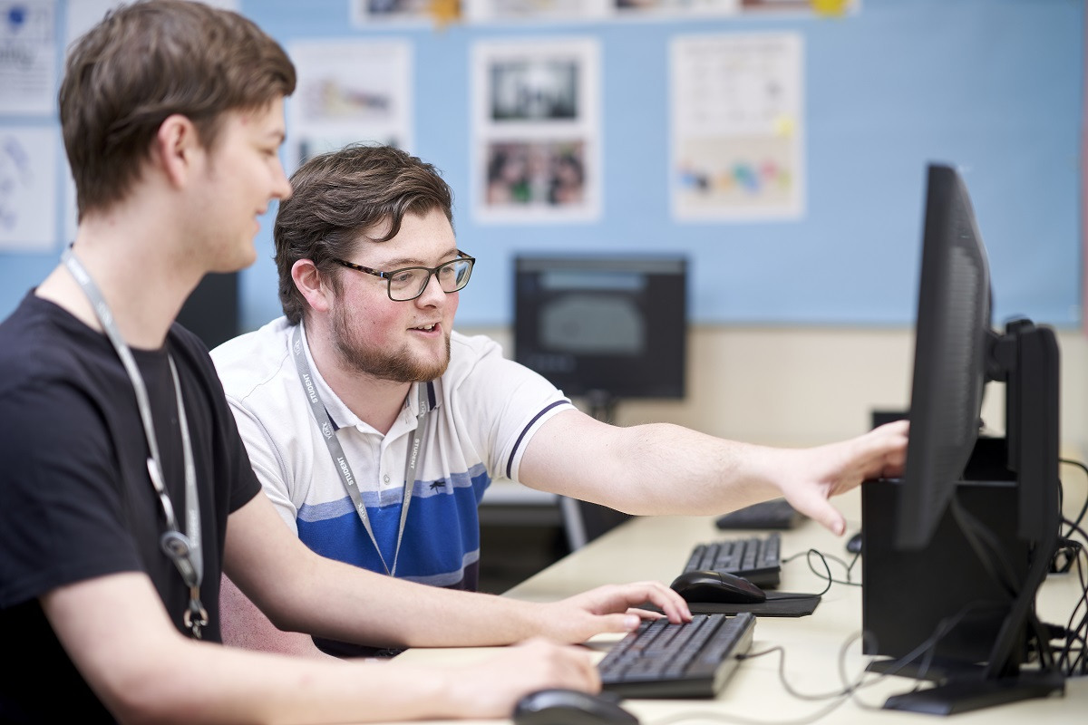 Two students discussing programming at a computer