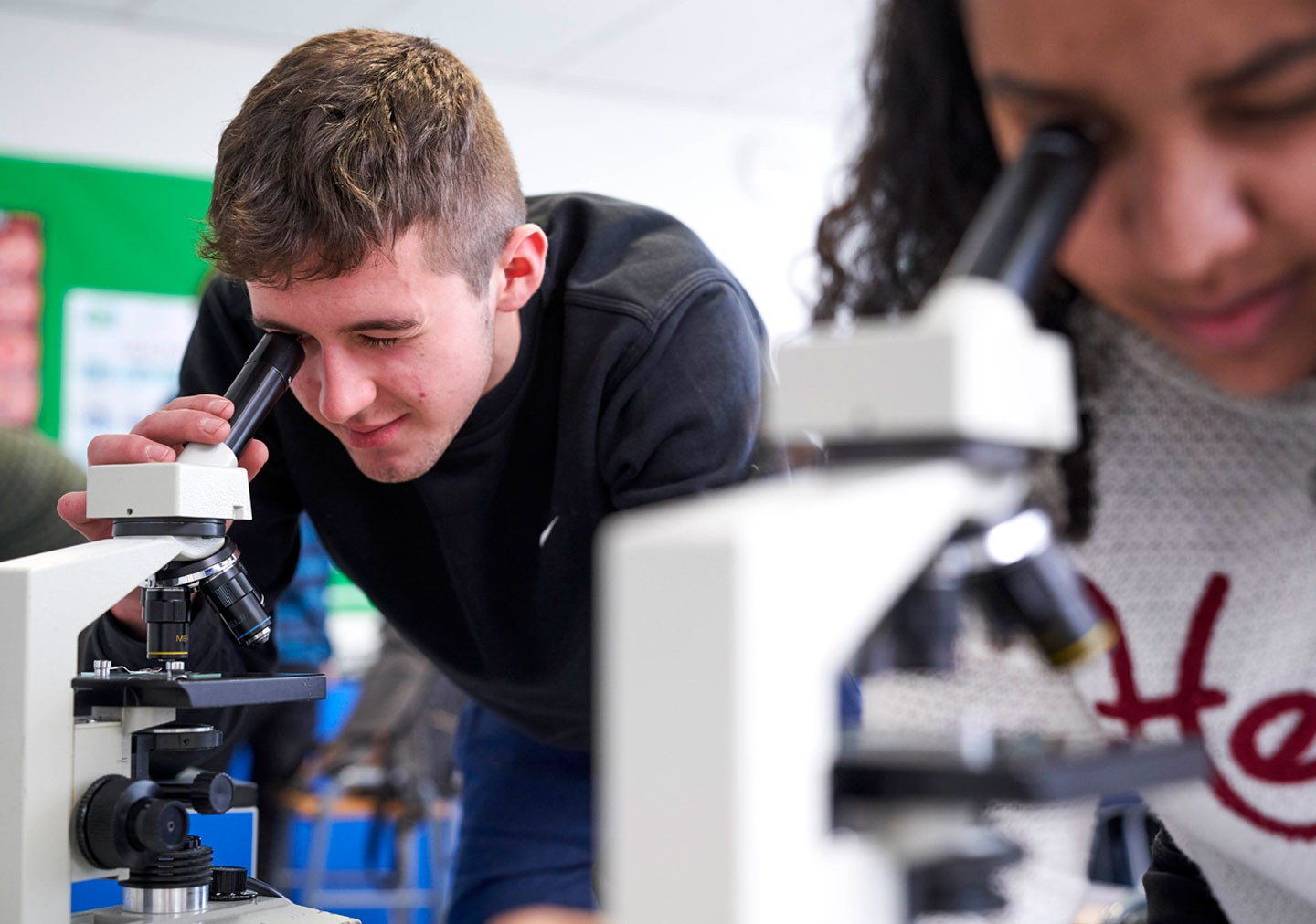 Two students look at samples under microscopes