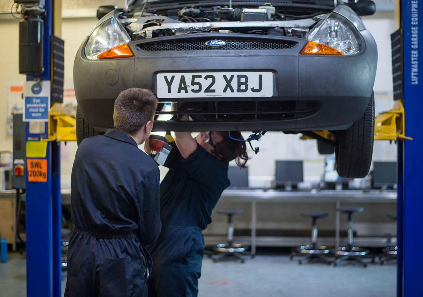 Two students working on a car raised on the vehicle ramps in the workshop