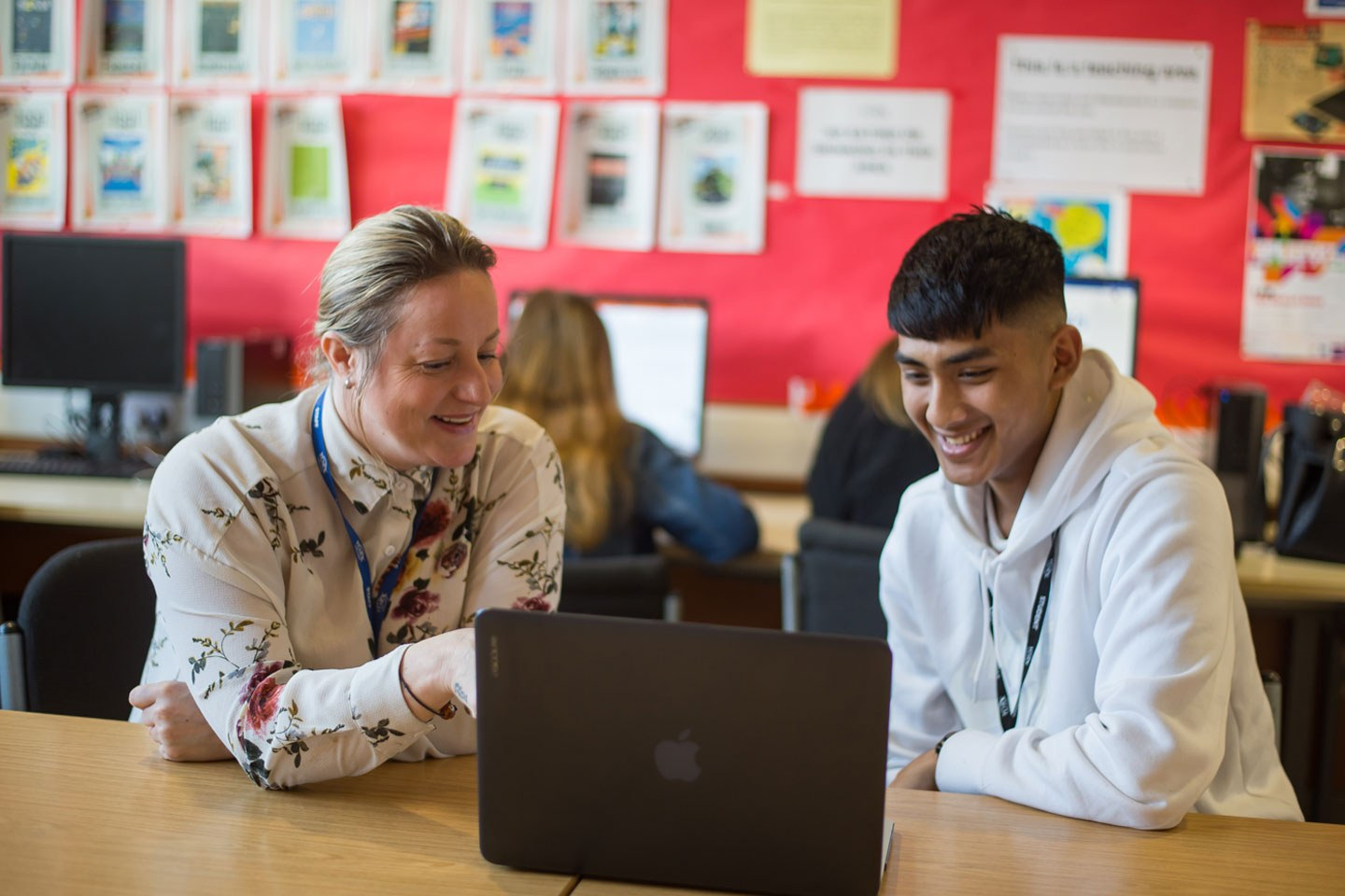 A tutor points to a laptop screen while the student watches, they both smile.