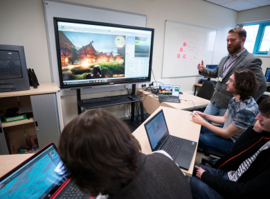 A tutor discusses a video game displayed on a large screen with three students