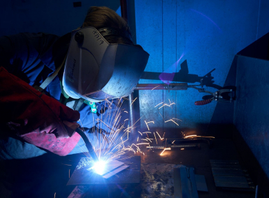 A student welding in the workshop