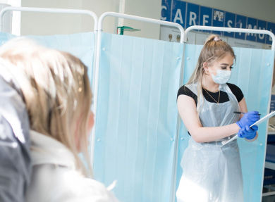 Two Health and Social care students in a mock-up situation of patient and carer