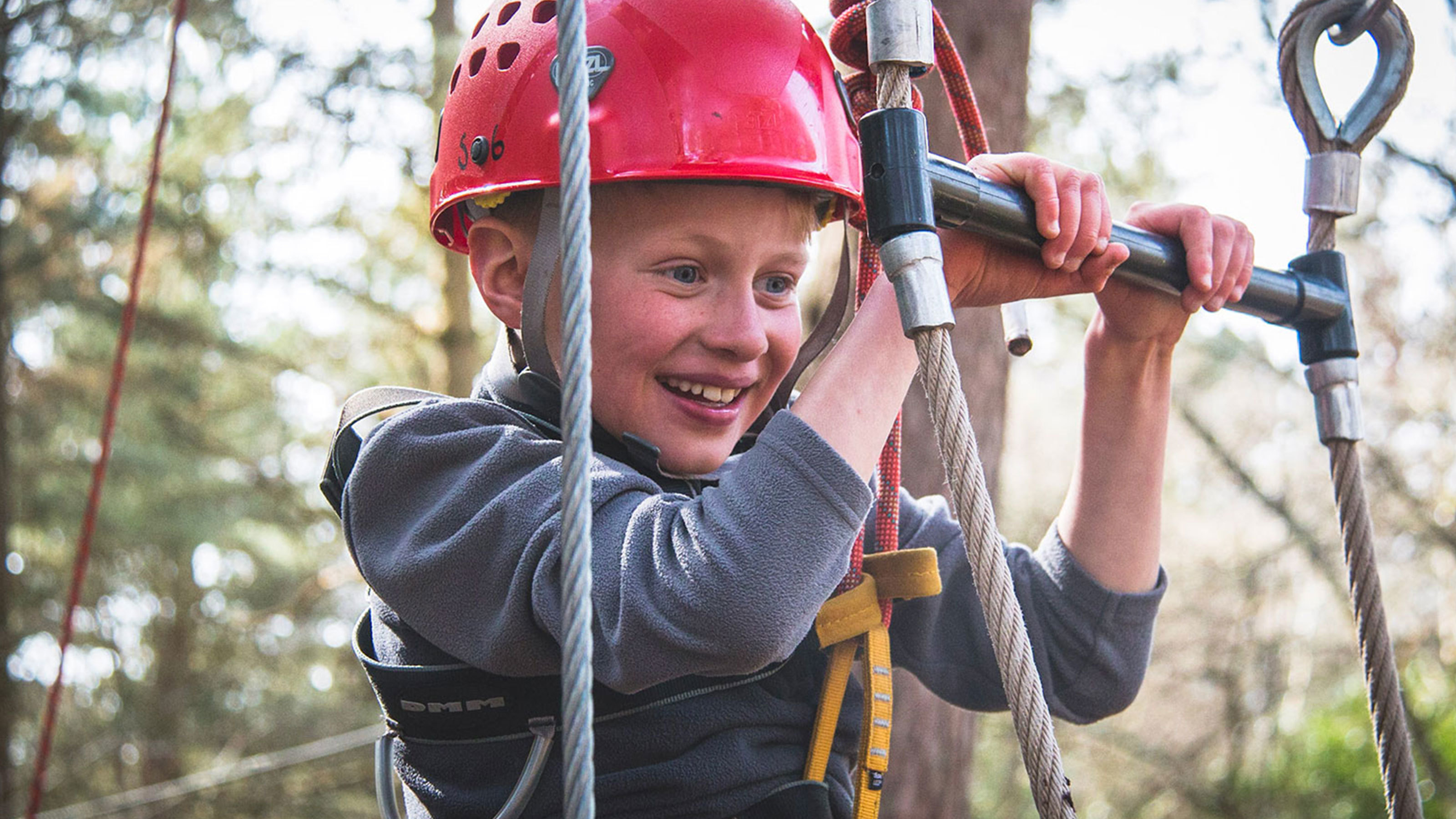 A young boy smiles on the High Ropes challenge