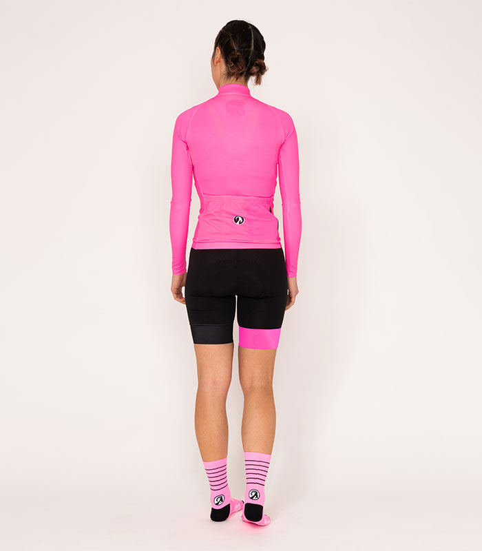 nicole pugson wears the stolen goat core fitch pink bodyline jersey and shorts and pink coolmax socks while posing in the studio facing backwards